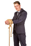 Businessman tied up in rope. Isolated on white Stock Photo
