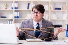 The businessman tied up with rope in office. Businessman tied up with rope in office Royalty Free Stock Photos