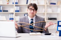 The businessman tied up with rope in office Stock Photos