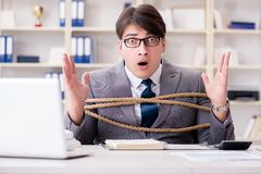 The businessman tied up with rope in office. Businessman tied up with rope in office Stock Photography