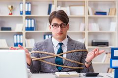 The businessman tied up with rope in office. Businessman tied up with rope in office Stock Photos