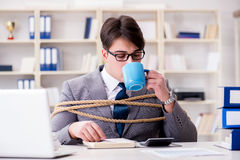 The businessman tied up with rope in office. Businessman tied up with rope in office Royalty Free Stock Image