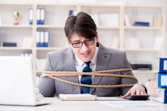 The businessman tied up with rope in office. Businessman tied up with rope in office Royalty Free Stock Photo