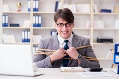 The businessman tied up with rope in office. Businessman tied up with rope in office Stock Image