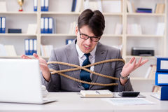 The businessman tied up with rope in office. Businessman tied up with rope in office Stock Photo
