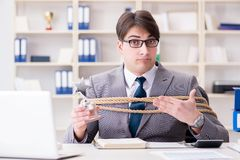 The businessman tied up with rope in office. Businessman tied up with rope in office Royalty Free Stock Photography