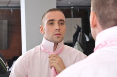 Businessman ties his neck-tie stock photo
