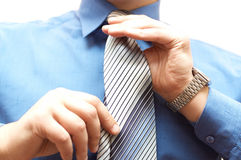 Businessman ties his neck tie Stock Photos