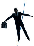 Businessman  tightrope walker silhouette. One caucasian Businessman  tightrope walker in silhouette studio isolated on white background Stock Images