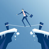 Businessman tightrope walker. Is walking a tightrope across the gap in the rocks, an employee is walking a tightrope between two cliffs, business concept risk Stock Photos