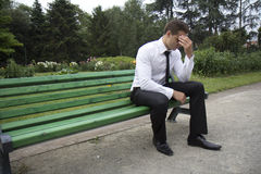 Businessman tired. Young businessman sitting on a bench. It looks like he is tired royalty free stock photography