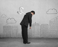 Businessman tired with money winder on his back. With clouds and city buildings doodles background Stock Images