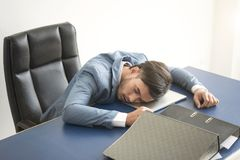 Businessman tired overworked sleeping over a laptop in office. Desk Royalty Free Stock Photography