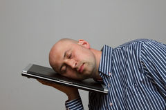 Businessman tiring and sleeping on his laptop in outdoor scene - overworked concept. On a gray background Stock Photo