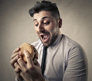 Businessman about to eat a hamburger Stock Images