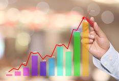 Businessman to point in peak of Business graph on abstract blur. Background,Concept financial symbols coming success and profitability stock images