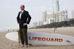 Businessman to the Rescue. Humorously symbolic photo of a man in business suit, standing with a lifeguard's rescue surfboard and scanning the water for someone Stock Photos