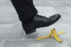 Businessman stepping on banana skin in street, banana peel accident. Businessman about to step on a banana skin or peel.  Accident Royalty Free Stock Photos