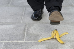 Banana peel accident : businessman about to step on a banana skin, copy space Stock Image