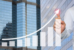 Businessman to touch in peak of Business graph on Skyscraper background. Businessman to touch in peak of Business graph on Skyscraper background,Concept stock image
