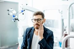 Businessman with toothache in the dental office stock image