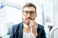 Businessman with toothache in the dental office stock photo