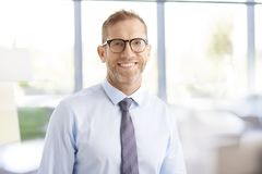 Businessman with toothy smile. Portrait of happy middle aged businessman wearing shirt and tie while standing at the office Royalty Free Stock Photography