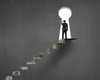 Businessman on top of money stairs with key hole Royalty Free Stock Photography