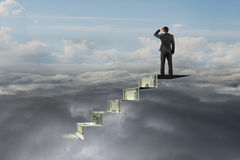 Businessman on top of money stairs looking at natural cloudscape Stock Image