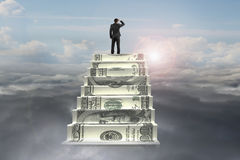 Businessman on top of money stairs looking at sunlight cloudscap Stock Photography
