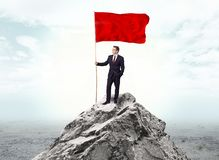 Businessman on the top of a the mountain holding flag stock images