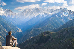 The businessman at the top of the mountain sitting and thinking Royalty Free Stock Photography