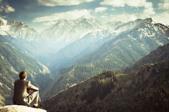 Businessman at the top of the mountain sitting and thinking Stock Images