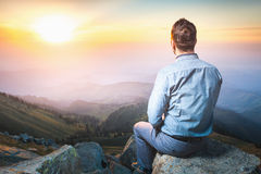 Businessman at the top of the mountain sitting and thinking. Image of a young businessman who sits on the top of the mountain and looks into the distance to the Stock Image