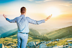Businessman at the top of the mountain sitting and thinking Royalty Free Stock Photo