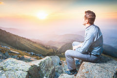 Businessman at the top of the mountain sitting and thinking Royalty Free Stock Images