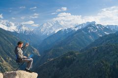 The businessman at the top of the mountain using wireless networ Stock Images