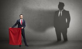 Businessman with toreador concept and his shadow on the background stock photography