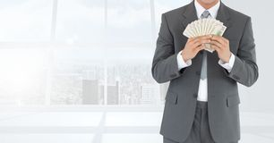 Businessman Torso holding bills against windows. Digital composite of Businessman Torso holding bills against windows Stock Image