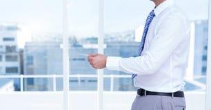 Businessman Torso holding a pen against windows Stock Images