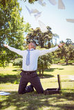 Businessman tossing papers in the park Royalty Free Stock Images