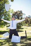 Businessman tossing papers in the park Royalty Free Stock Photos