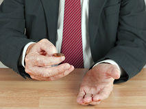 Businessman tossing UK coin at desk Royalty Free Stock Photo