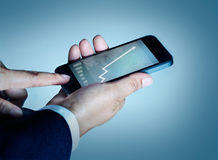 Businessman touch mobile phone graph and statistics rising on sc Royalty Free Stock Photos