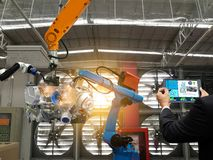 Businessman touch screen control robot the production of factory parts engine manufacturing industry robots stock image
