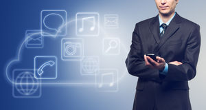 Businessman with touch screen phone and the cloud with applications icons on blue. Background royalty free stock photo