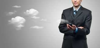 Businessman with touch screen phone and the clouds. On grey background royalty free stock photography