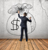 Businessman touches a sketch of money bag on concrete wall. Royalty Free Stock Photography