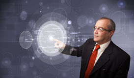 Businessman touching abstract high technology circular buttons. Elegant businessman touching abstract high technology circular buttons Stock Images
