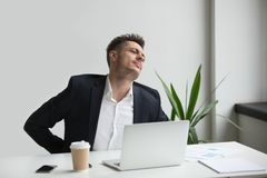 Businessman touching aching back feeling backache after sedentar. Upset businessman touching aching back feeling strong backache pain in tensed muscles sitting Stock Images